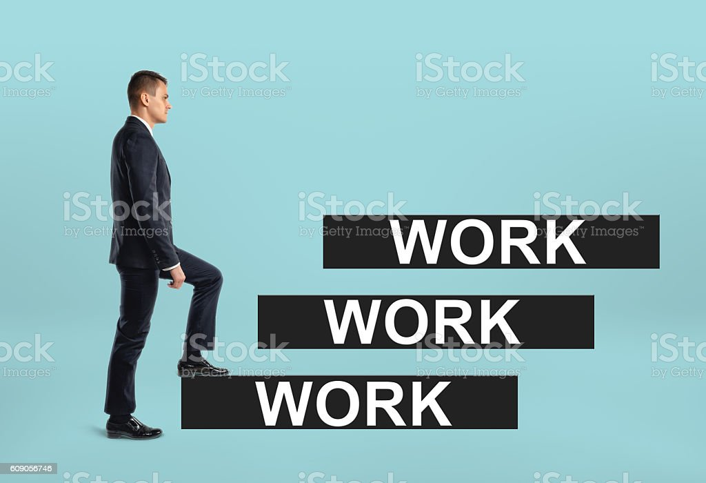 Side view of a businessman stepping up career ladder with stock photo