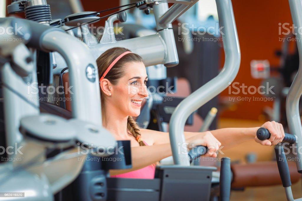 Vista lateral de uma mulher alegre, exercendo durante a rotina de exercícios da parte superior do corpo - Foto de stock de Academia de ginástica royalty-free