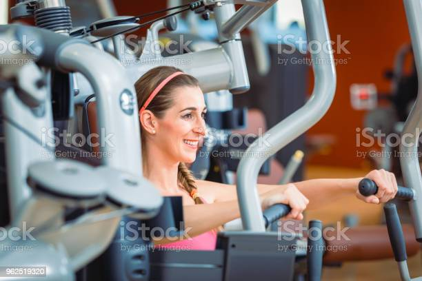 Foto de Vista Lateral De Uma Mulher Alegre Exercendo Durante A Rotina De Exercícios Da Parte Superior Do Corpo e mais fotos de stock de Academia de ginástica