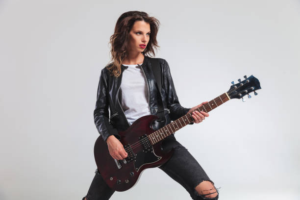 side view of a cool woman guitarist playing electric guitar - punk music stock photos and pictures