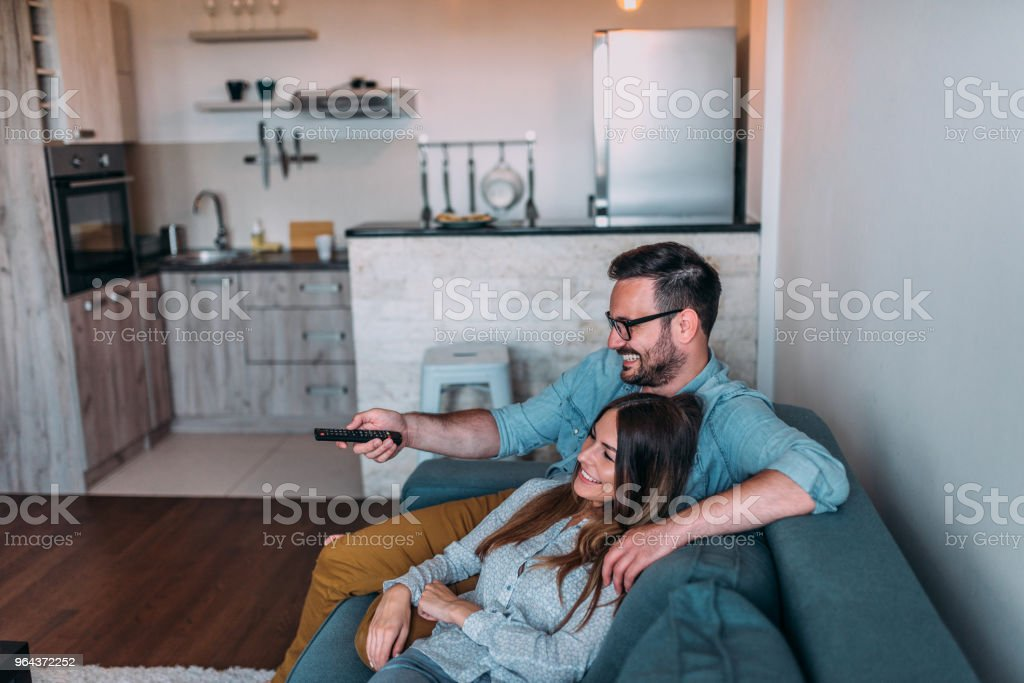 Zijaanzicht van een paar lettend op een film thuis. - Royalty-free Afgelegen Stockfoto