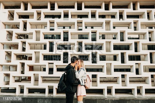 istock Side view of a cute caucasian couple embracing and smiling against a beautiful wall outside in the city while dating. 1137015735