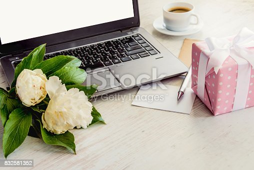 istock Side view of a deck with computer, bouquet of peonies flowers, cup of coffee, empty card and pink dotted gift box. White rustic wooden background. Romantic and feminine outlook. 832581352