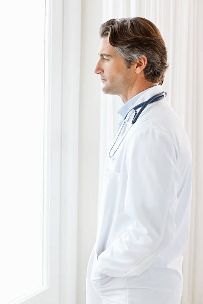 Side view of a doctor standing in thought by the window stock photo