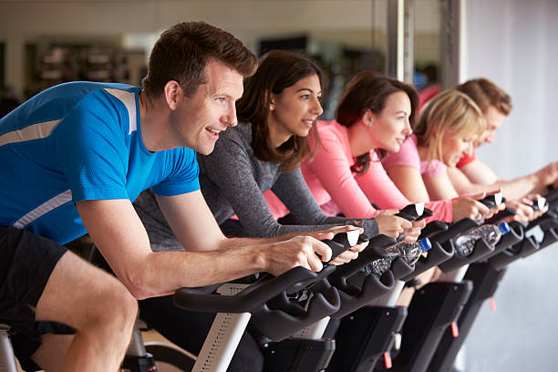 Side view of a exercising class on exercise bikes at Side view of a exercising class on exercise bikes at a gym exercise bike stock pictures, royalty-free photos & images