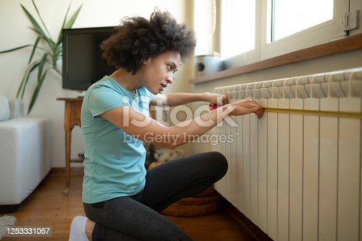 Young female African American interior designer using a measurement tape at home before proceeding with the DIY home improvement