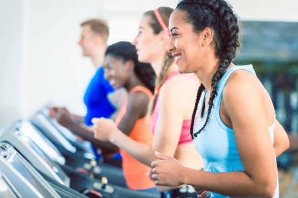 Seitenansicht einer Fit glücklich Frau und ihre Trainingsgruppe auf Laufband im Fitness-Studio – Foto