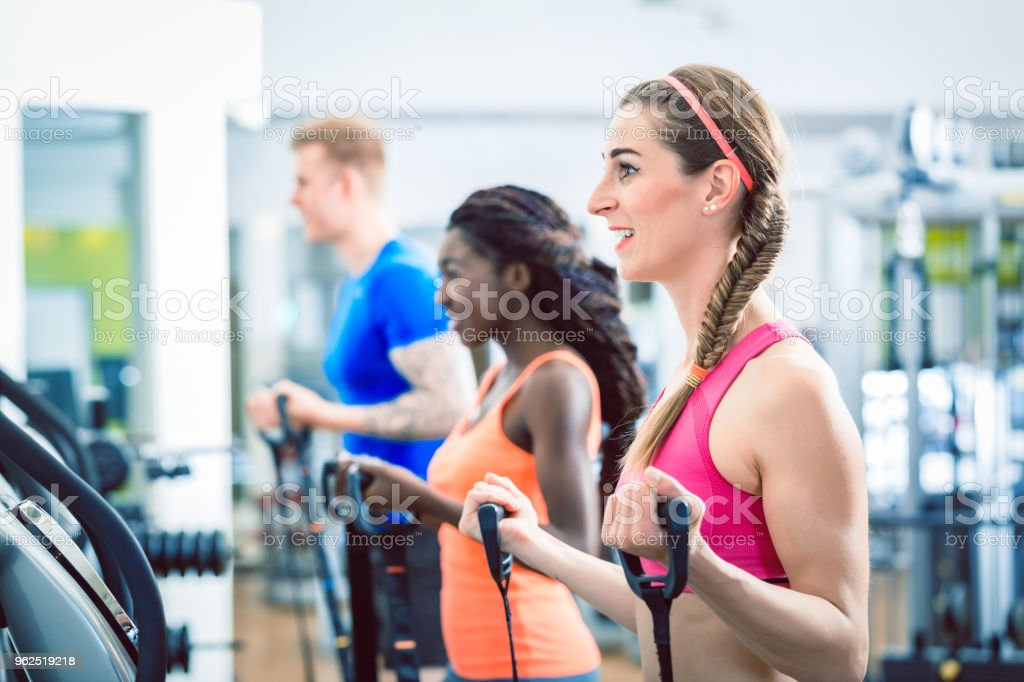 Side view of a fit happy woman cycling during cardio workout routine at the gym - Royalty-free Adult Stock Photo