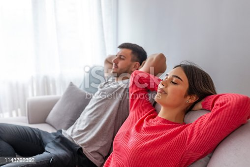 938682762istockphoto Side view of a happy couple breathing and resting lying in a couch at home with a window in the background 1143762392