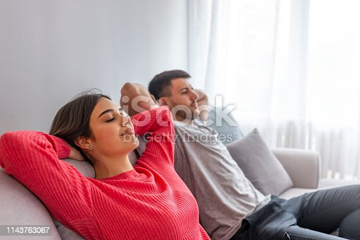 938682762istockphoto Side view of a happy couple breathing and resting lying in a couch at home with a window in the background 1143763067