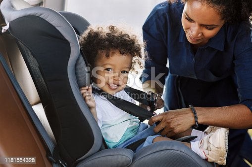Side view of a happy little boy looking at camera while his mother buckling him in a car seat