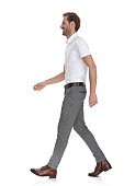istock side view of a happy young man walking forward 1131989347