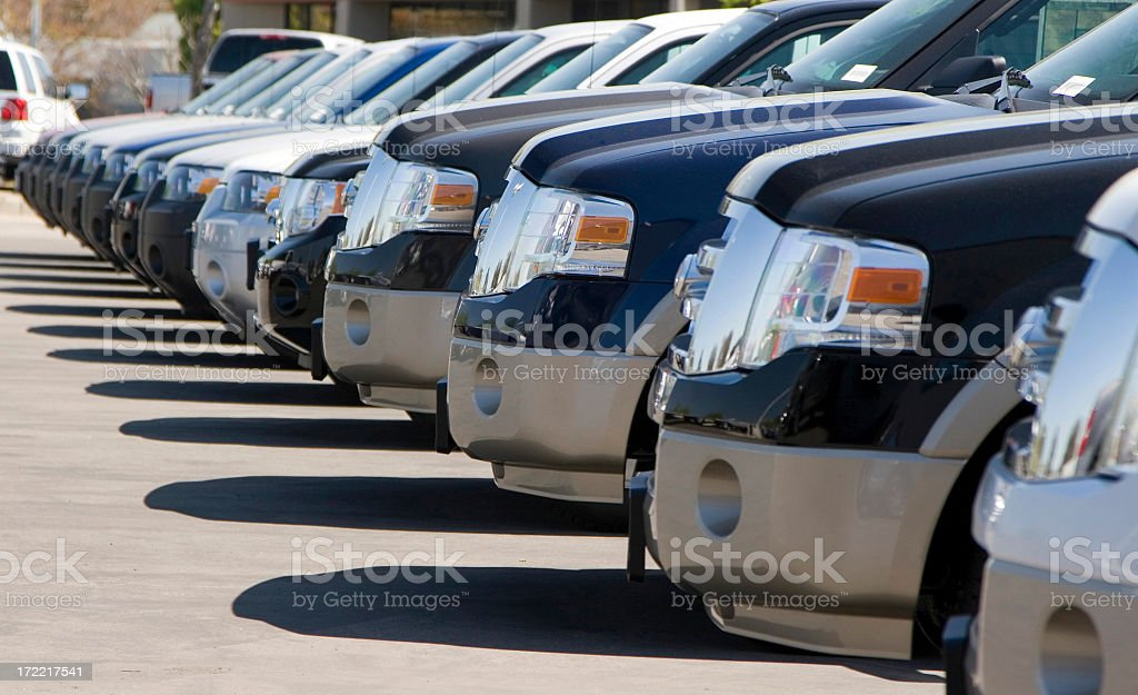 Side view of a long row of automobile front bumpers in a lot stock photo