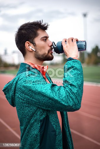 Side view of a male drinking fresh water from a bottle during training. Water intake concept