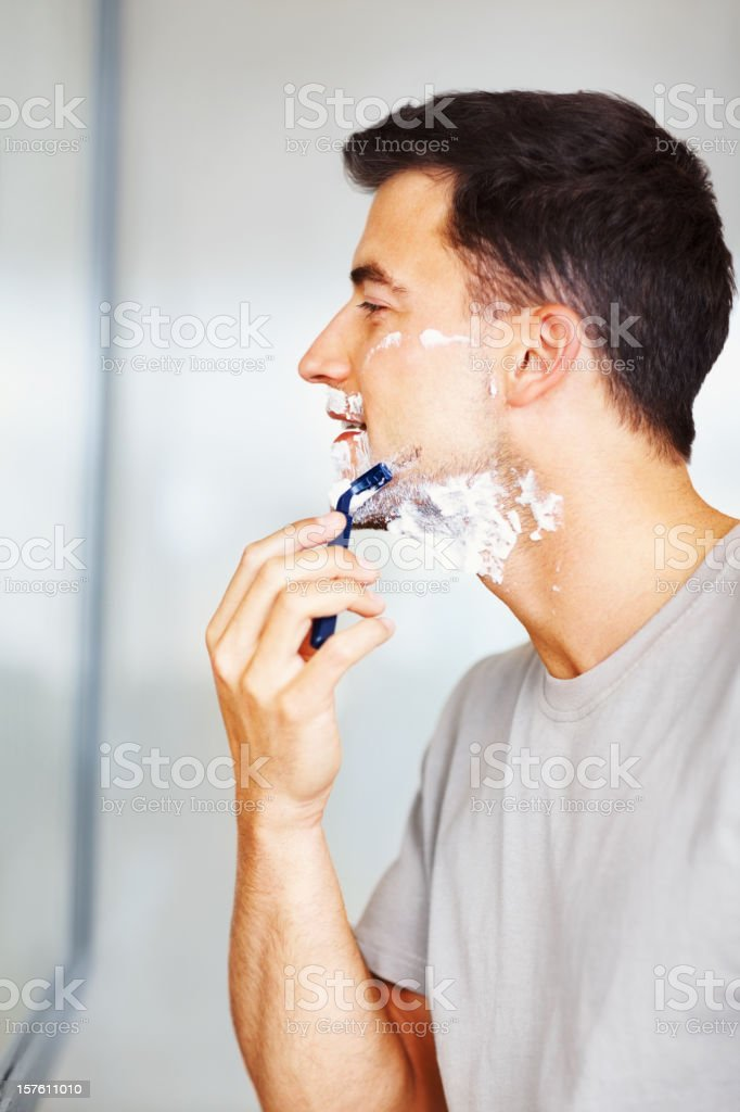 Side view of a male looking at mirror and shaving royalty-free stock photo