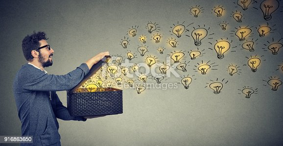 istock Side view of a man holding box with brilliant ideas being creative 916863650