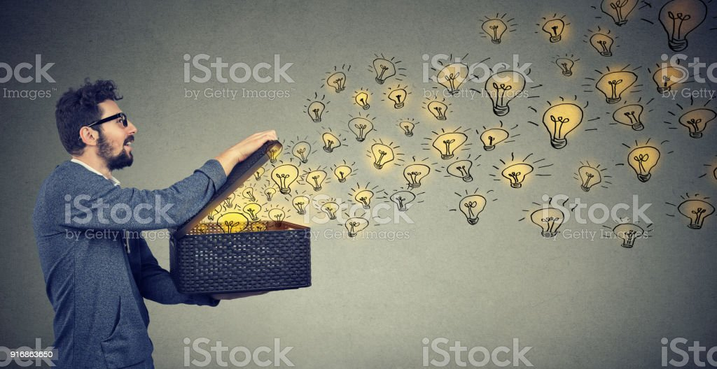 Side view of a man holding box with brilliant ideas being creative stock photo