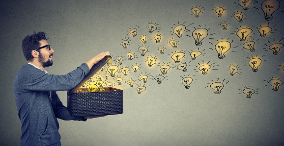 Side View Of A Man Holding Box With Brilliant Ideas Being Creative Stock Photo - Download Image Now