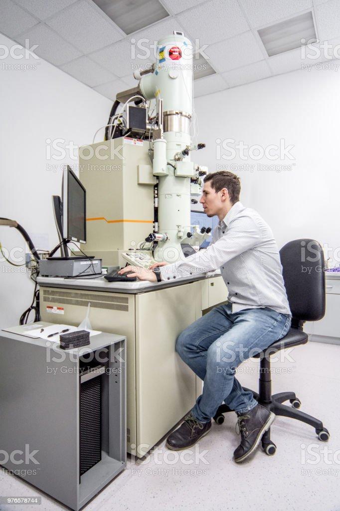 Vista lateral de un hombre usando Miscroscope de electrones de emisión de campo - foto de stock