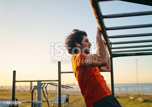 Sporty young man doing pull-ups in morning at the outdoors gym at his local park