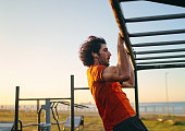 istock Side view of a muscular fit young man with earphones in his ears doing pull-ups at the outdoor gym in the park 1193234064