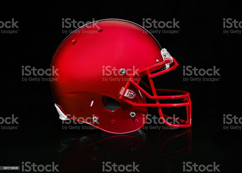 Side view of a red football helmet on a black background stock photo