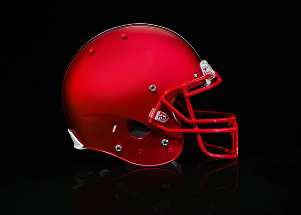 Side view of a red football helmet on a black background A Red American football helmet on a black background football helmet stock pictures, royalty-free photos & images
