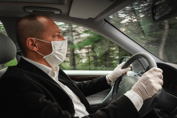 Side view of a senior adult wearing surgical mask and gloves driving his car stock photo
