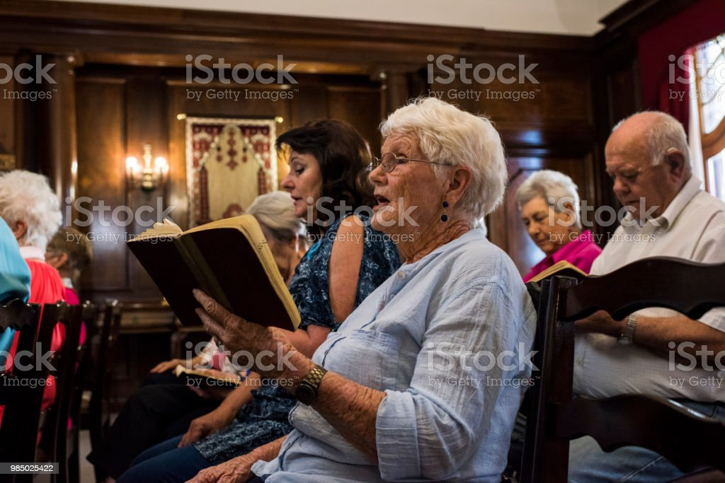 Side view of a senior women singing in church stock photo