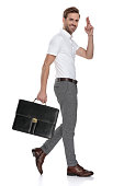 istock side view of a smiling  man holding briefcase and greets 1131990186