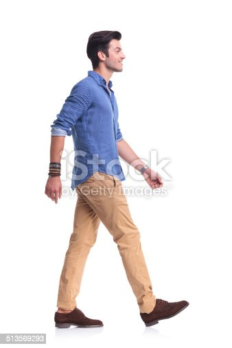 istock side view of a smiling young casual man walking 513569293