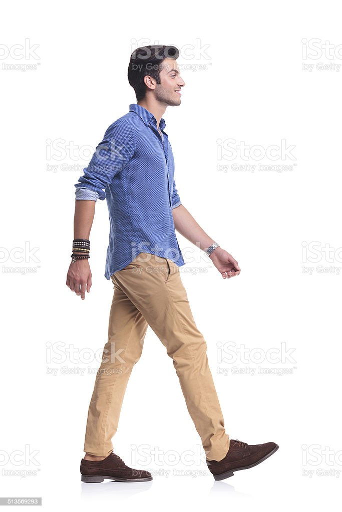 side view of a smiling young casual man walking stock photo