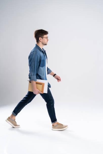 Seitenansicht eines lächelnden jungen lässigen Mannes zu Fuß, Student mit Buch ang Notizen auf weißem Hintergrund. – Foto