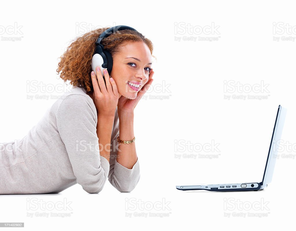 Side view of a smiling young lady with headphones and laptop isolated on white background stock photo