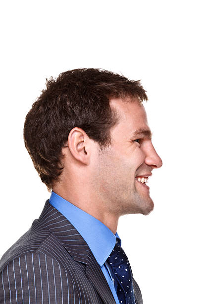 Side view of a suited man grinning stock photo