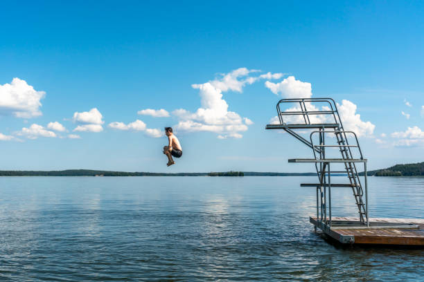 Side view of a teenage male jump diving from a diving tower with blue sky and horizon in the background. stock photo