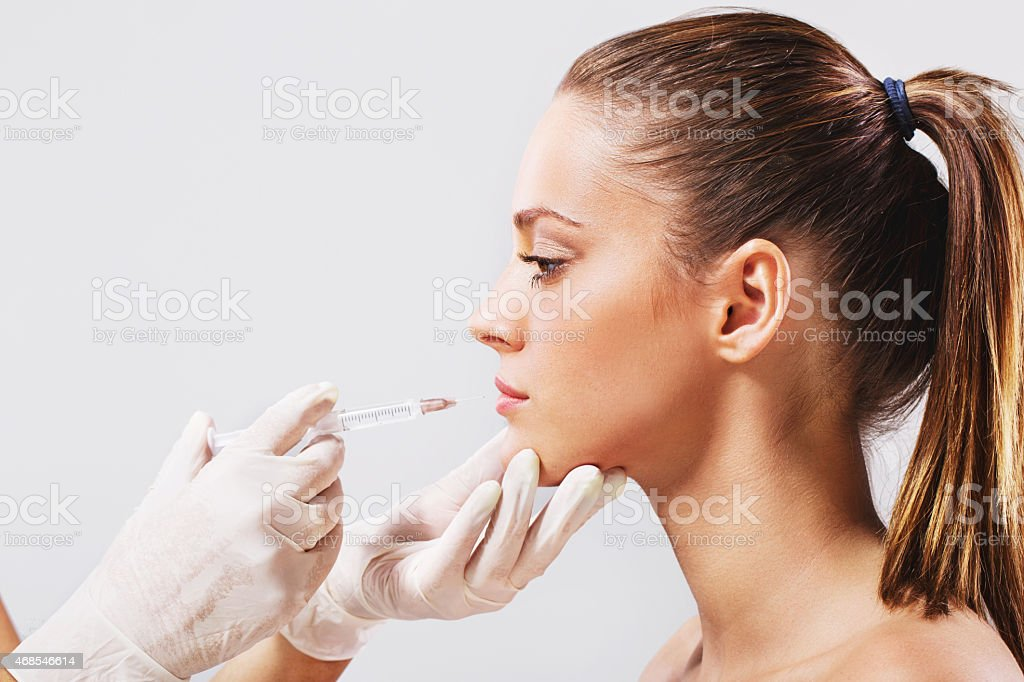 Side view of a treatment with Botox injection. stock photo