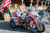 Side view of a trike motorcycle showing the USA flag colors in a parking lot during day of summer time in Arudel, Maine