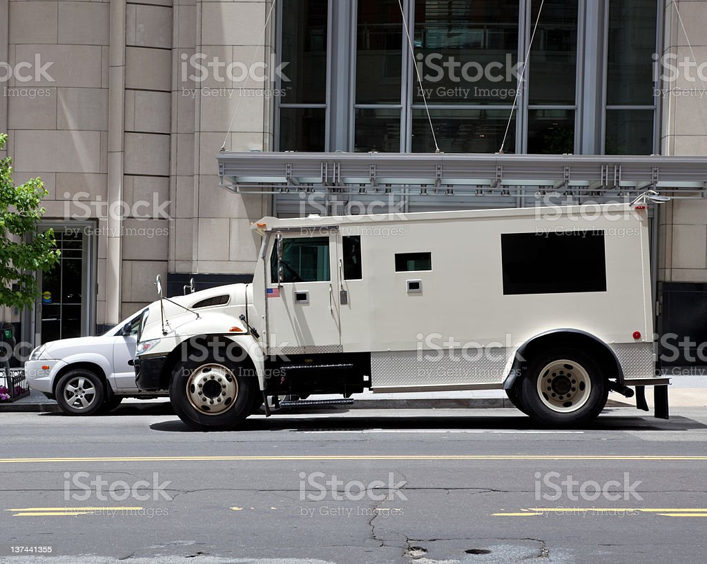 Side view of a white armoured truck parked on street stock photo