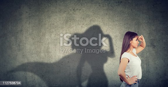 istock Side view of a woman imagining to be a super hero looking aspired. 1127538704