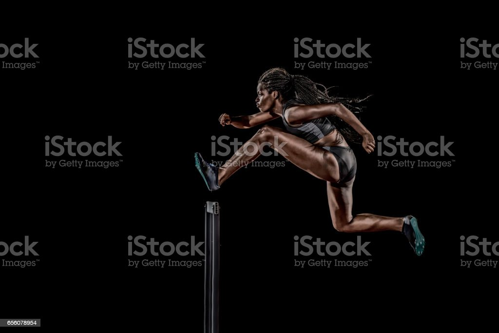 Side view of a woman jumping over a hurdle stock photo