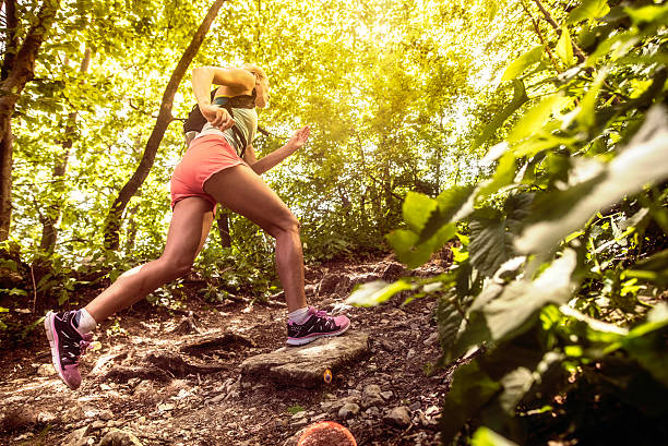 side view of a woman running uphill in a forest - jogging hill bildbanksfoton och bilder