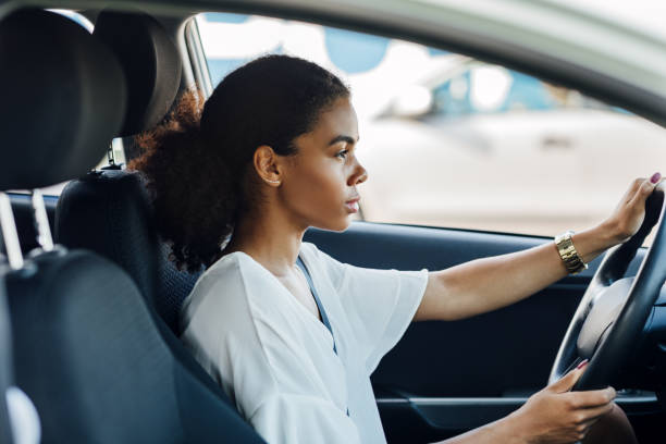 Side view of a woman sitting in a car holding a steering wheel and looking on the road stock photo