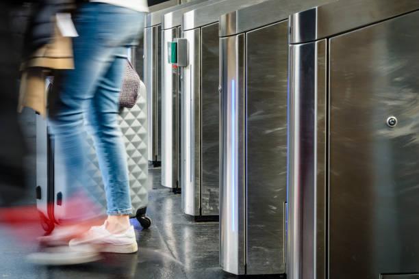 seitenansicht einer frau mit einem rollenden koffer durch edelstahl ticket tore in einem öffentlichen verkehrsmittel station in paris, frankreich, mit motion blur. - trolley kaufen stock-fotos und bilder
