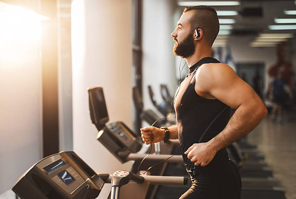 Side view of a young athlete running on treadmill. Young muscular man jogging on treadmill in a gym. treadmill stock pictures, royalty-free photos & images