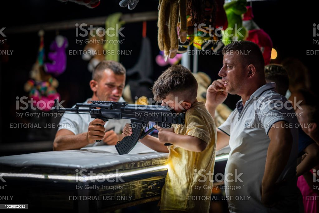 Side view of a young boy and father shooting with airsoft automatic weapon at a fair. stock photo