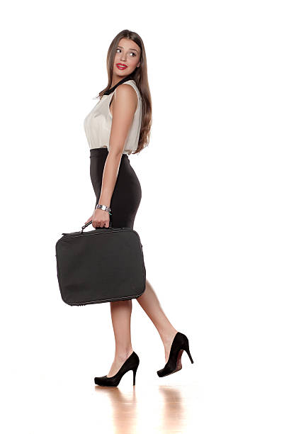 side view of a young business woman walking on white side view of a young business woman in a skirt with a bag, walking on white beautiful sexy girls stock pictures, royalty-free photos & images