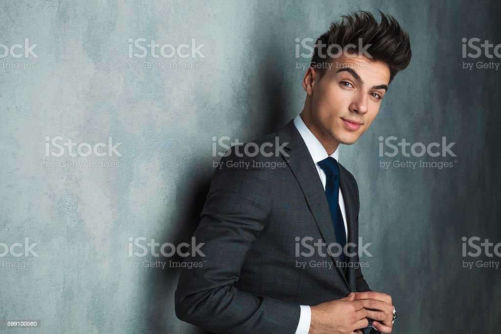 side view of a young businessman buttoning his suit ストックフォト