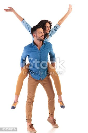 854381886 istock photo side view of a young casual couple celebrating success 854378134
