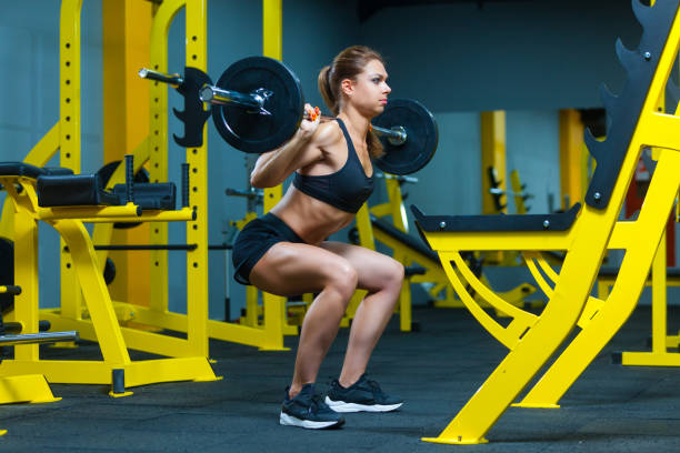 Side view of a young fitness woman doing barbell squats in a gym stock photo